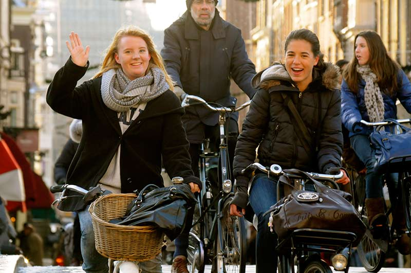 Two young ladies riding bikes in a city, one of them waving at the camera.